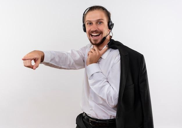 Homem de negócios bonito segurando uma jaqueta sobre o ombro com fones de ouvido e um microfone olhando para a câmera, sorrindo alegremente apontando com o dedo para algo em pé sobre um fundo branco