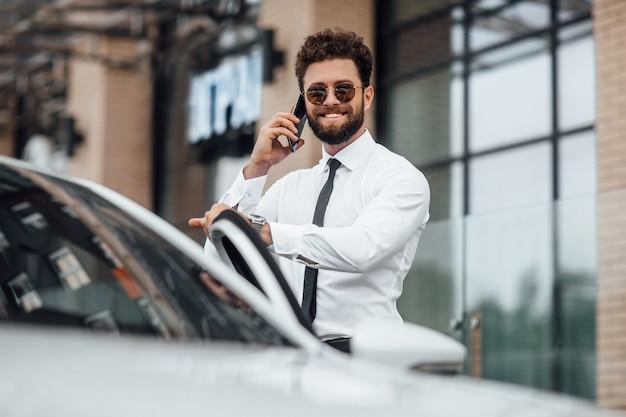 Homem de negócios bonito, sorridente e barbudo de camisa branca, falando por telefone e em pé perto de seu carro ao ar livre nas ruas da cidade perto do moderno centro de escritórios