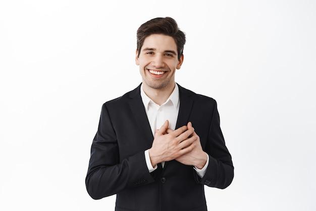 Homem de negócios bonito sorridente em terno preto de mãos dadas no coração e olhando atencioso e sincero na frente, em pé sobre uma parede branca