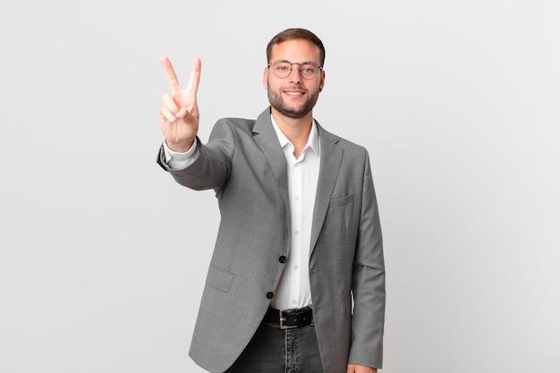 Homem de negócios bonito sorrindo e parecendo feliz, gesticulando vitória ou paz