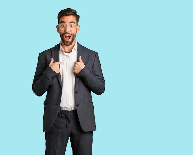 Homem de negócios bonito surpreso, sente-se bem sucedido e próspero