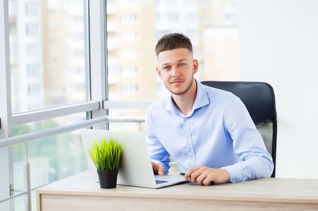 Homem de negócios bonito trabalhando com o laptop no escritório.