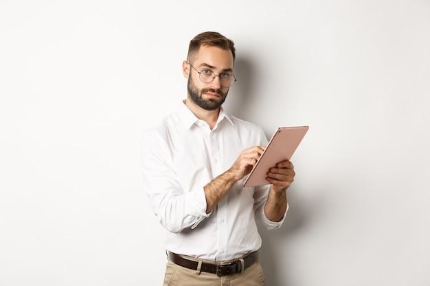 Homem de negócios bonito trabalhando em tablet digital, lendo algo, em pé