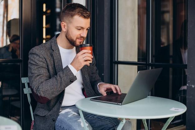 Homem de negócios bonito trabalhando em um laptop em um café