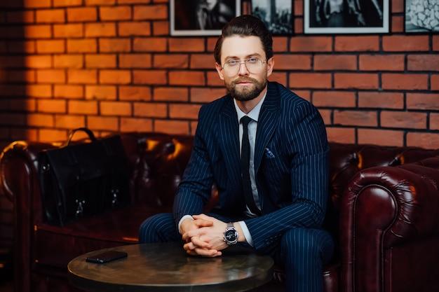 Homem de negócios bonito usando óculos da moda e elegante terno sentado no sofá no estúdio moderno.