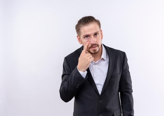 Homem de negócios bonito usando terno apontando com o dedo no olho e vendo seu gesto de pé sobre um fundo branco