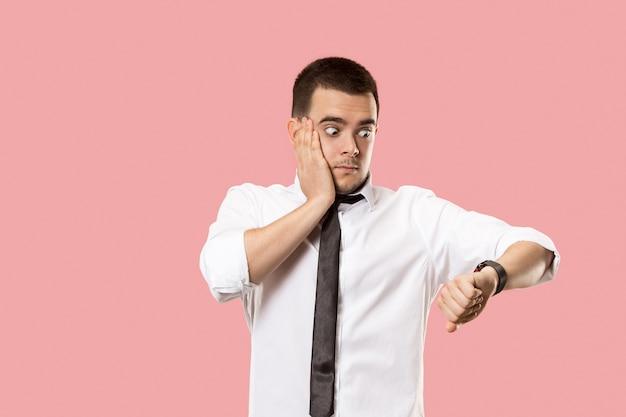 Homem de negócios bonito verificando seu relógio de pulso isolado em rosa
