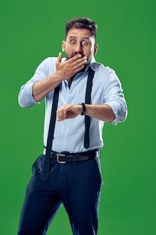Homem de negócios bonito verificando seu relógio de pulso isolado em verde. uau. retrato de homem atraente com metade do corpo