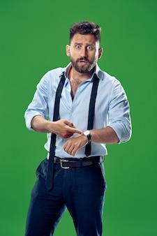 Homem de negócios bonito verificando seu relógio de pulso isolado em verde.