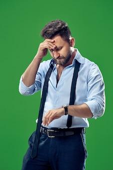 Homem de negócios bonito verificando seu relógio de pulso isolado no fundo branco