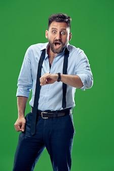 Homem de negócios bonito verificando seu relógio de pulso isolado sobre fundo verde. uau