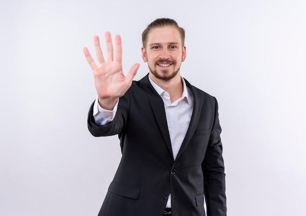 Homem de negócios bonito vestindo terno aparecendo e apontando para cima com os dedos número cinco em pé sobre um fundo branco