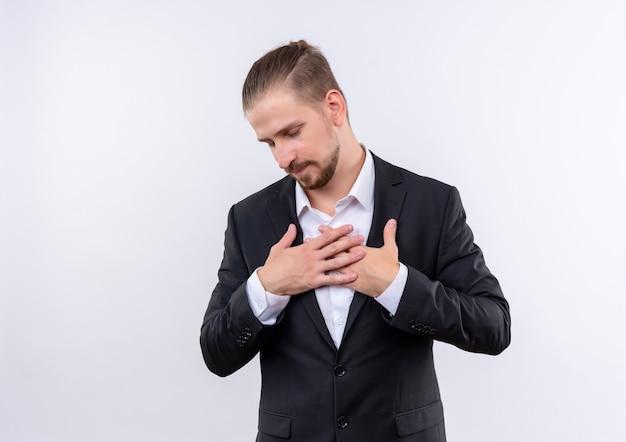 Homem de negócios bonito vestindo terno de mãos dadas no peito, sentindo emoções agradecidas e positivas com os olhos fechados, de pé sobre um fundo branco