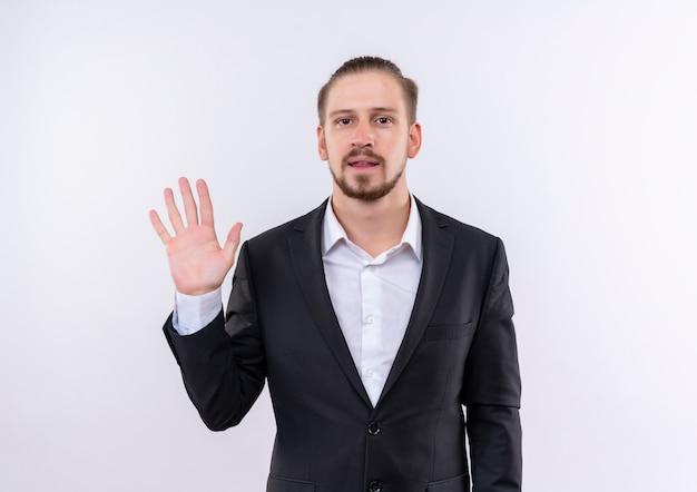 Homem de negócios bonito vestindo terno mostrando o número cinco e sorrindo confiante em pé sobre um fundo branco