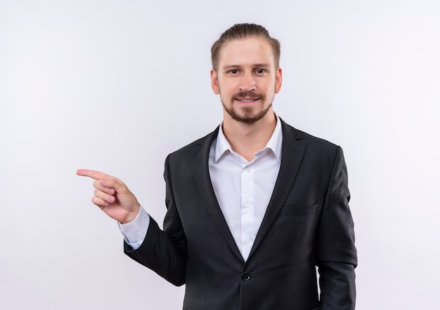 Homem de negócios bonito vestindo terno olhando para a câmera com um sorriso confiante apontando com o dedo indicador para o lado em pé sobre um fundo branco