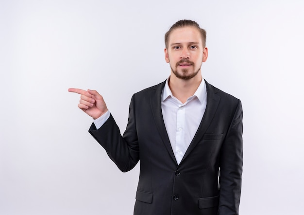 Homem de negócios bonito vestindo terno olhando para a câmera com um sorriso no rosto apontando com o dedo para o lado em pé sobre um fundo branco