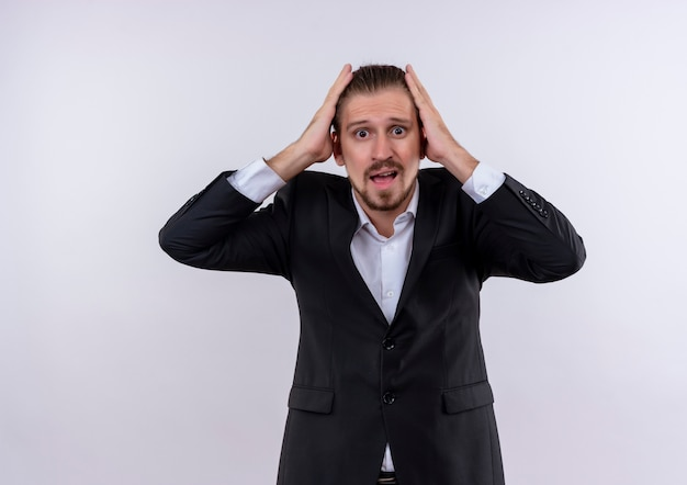 Homem de negócios bonito vestindo terno segurando a cabeça olhando para a câmera confuso em pé sobre um fundo branco
