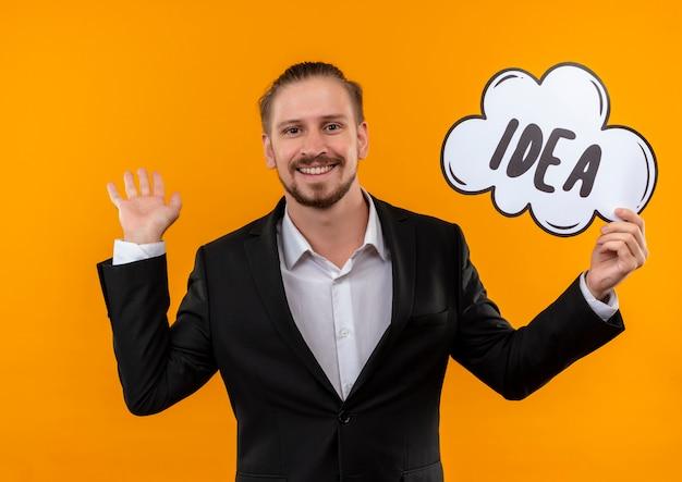 Homem de negócios bonito vestindo terno segurando a ideia da palavra em um balão de fala, olhando para a câmera, feliz e positivo, sorrindo alegremente em pé sobre um fundo laranja