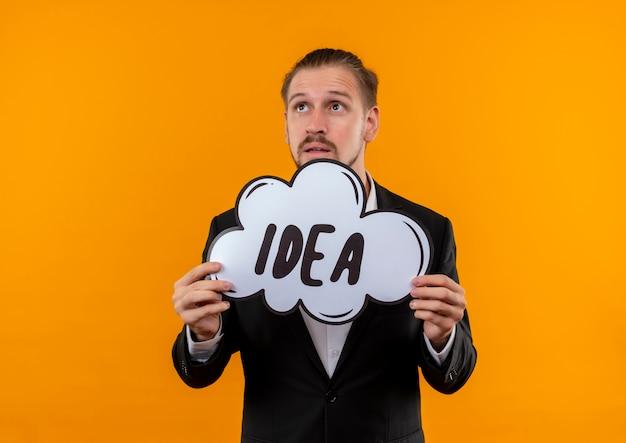 Homem de negócios bonito vestindo terno segurando a ideia da palavra em um balão de fala olhando para o lado perplexo em pé sobre fundo laranja