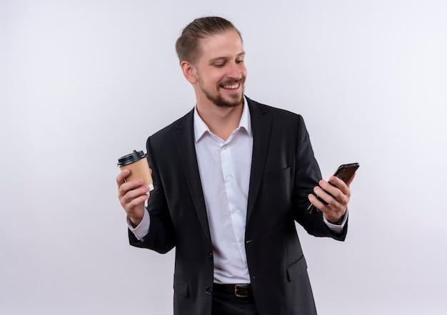 Homem de negócios bonito vestindo terno segurando smartphone e xícara de café em pé feliz e positivo sobre fundo branco