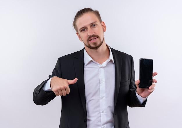 Homem de negócios bonito vestindo terno segurando um smartphone apontando com o polegar para ele, parecendo confiante em pé sobre um fundo branco