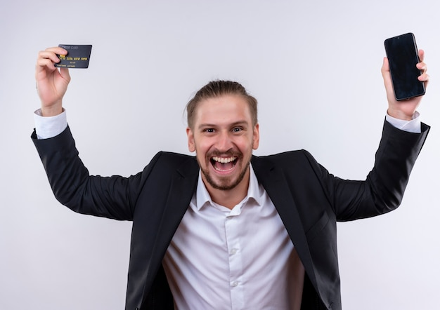 Homem de negócios bonito vestindo terno segurando um smartphone e um cartão de crédito em pé feliz e animado em pé sobre um fundo branco
