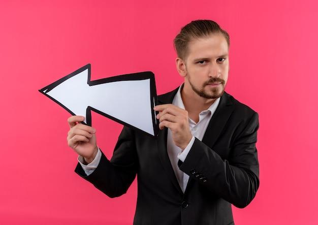 Homem de negócios bonito vestindo terno segurando uma seta apontando para a esquerda, olhando para a câmera com uma cara séria em pé sobre um fundo rosa
