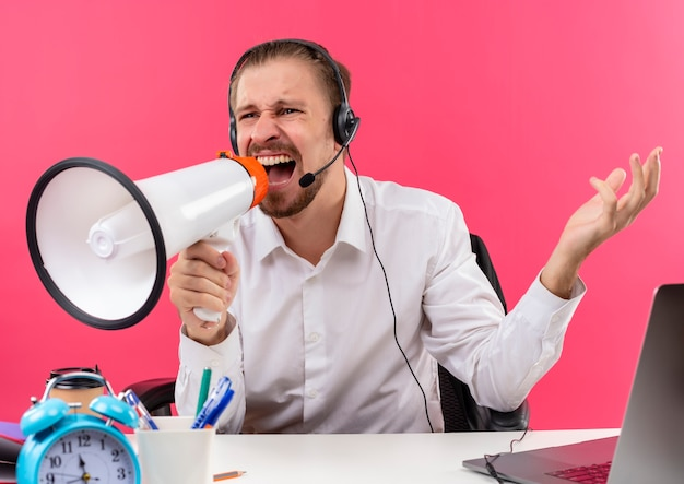 Homem de negócios bonito zangado de camisa branca e fones de ouvido com um microfone gritando para o megafone com expressão agressiva sentado à mesa em escritório sobre fundo rosa