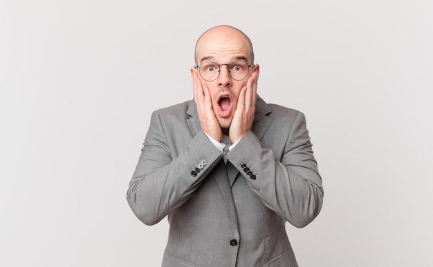 Homem de negócios careca chocado e assustado, parecendo apavorado com a boca aberta e as mãos nas bochechas