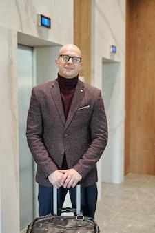 Homem de negócios careca e bem sucedido de terno e óculos segurando a mala pela alça enquanto fica em frente à câmera perto da porta do elevador