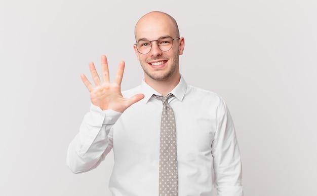 Homem de negócios careca sorrindo e parecendo amigável, mostrando o número cinco ou quinto com a mão para a frente, em contagem regressiva