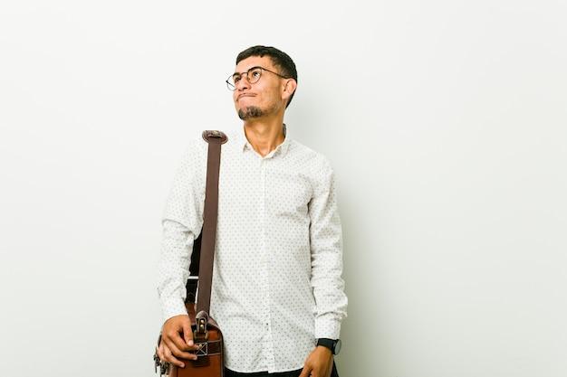 Homem de negócios casuais hispânico jovem sonhando em alcançar metas e propósitos