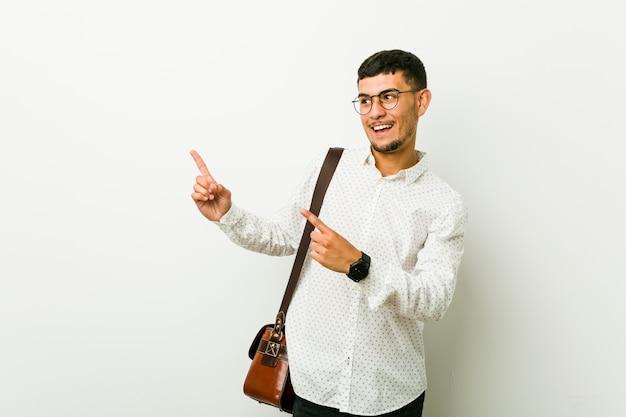Homem de negócios casuais latino-americanos jovens apontando com o dedo indicador para um espaço de cópia, expressando emoção e desejo.