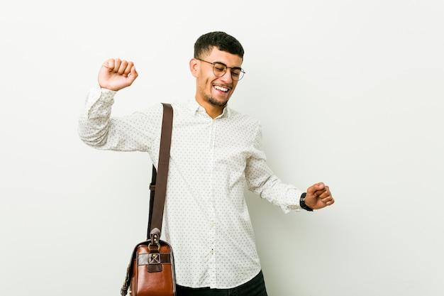 Homem de negócios casuais latino-americanos jovens comemorando um dia especial, saltos e levante os braços com energia.