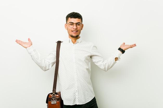 Homem de negócios casuais latino-americanos jovens faz le com braços, sente-se feliz e confiante.