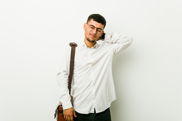 Homem de negócios casuais latino-americanos jovens que sofrem de dor de garganta devido ao estilo de vida sedentário.