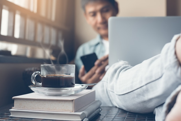 Homem de negócios casual asiático trabalhando em um laptop em casa