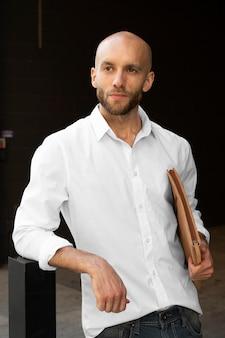 Homem de negócios casual com camisa branca a caminho do trabalho ao ar livre para uma sessão de fotos