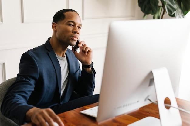 Homem de negócios casual falando ao telefone enquanto trabalha no escritório