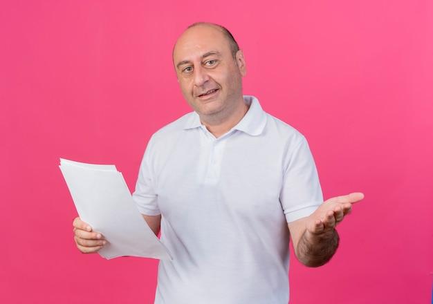 Homem de negócios casual maduro satisfeito segurando documentos e mostrando a mão vazia isolada em um fundo rosa