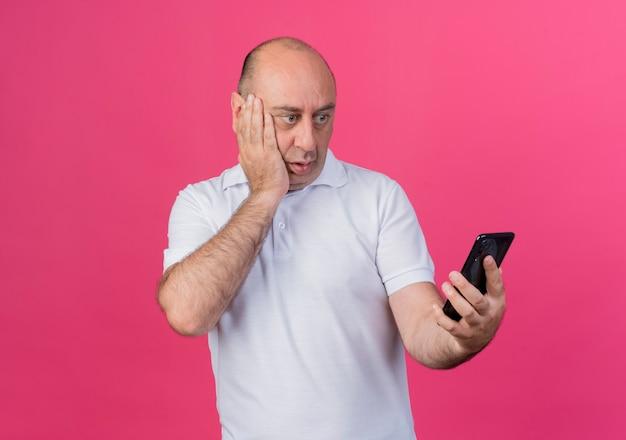 Homem de negócios casual maduro surpreso segurando e olhando para o celular e mantendo a mão no rosto isolado em um fundo rosa com espaço de cópia