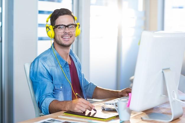 Homem de negócios casual trabalhando com digitalizador e ouvindo música