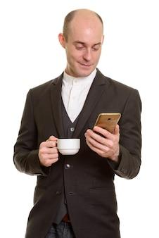 Homem de negócios caucasiano careca feliz sorrindo enquanto segura um telefone celular