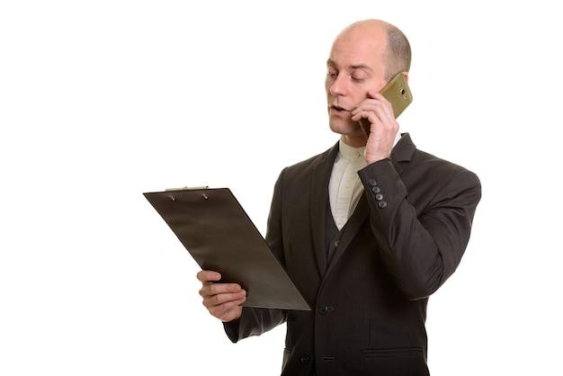 Homem de negócios caucasiano careca lendo na prancheta enquanto fala