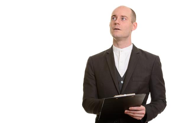 Homem de negócios caucasiano careca segurando a prancheta enquanto pensa