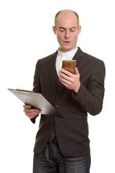 Homem de negócios caucasiano careca segurando a prancheta enquanto usa o celular