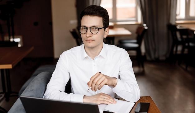 Homem de negócios caucasiano com óculos, olhando para a câmera enquanto trabalhava em um restaurante com um livro e um laptop