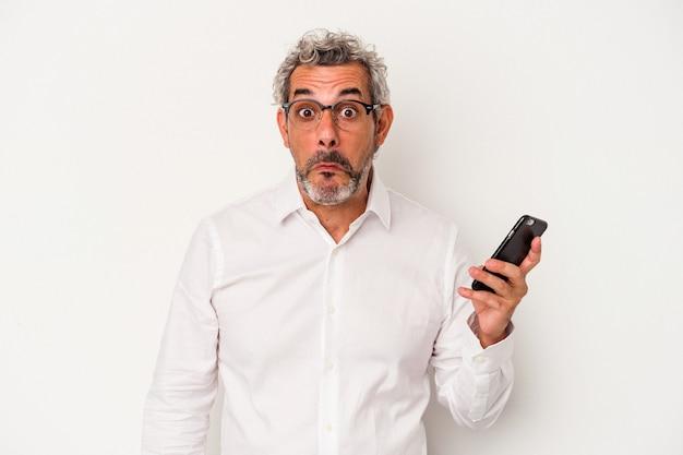 Homem de negócios caucasiano de meia-idade segurando um telefone celular isolado no fundo branco encolhe os ombros e abre os olhos confusos.