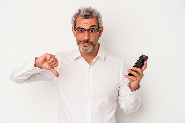 Homem de negócios caucasiano de meia-idade segurando um telefone celular isolado no fundo branco, mostrando um gesto de antipatia, polegares para baixo. conceito de desacordo.