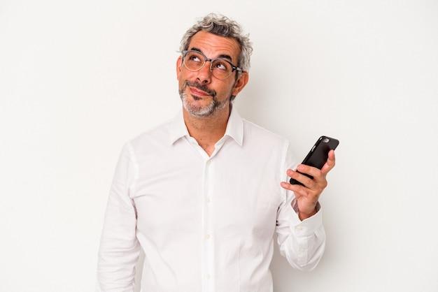 Homem de negócios, caucasiano, de meia-idade, segurando um telefone celular isolado no fundo branco, sonhando em alcançar objetivos e propósitos